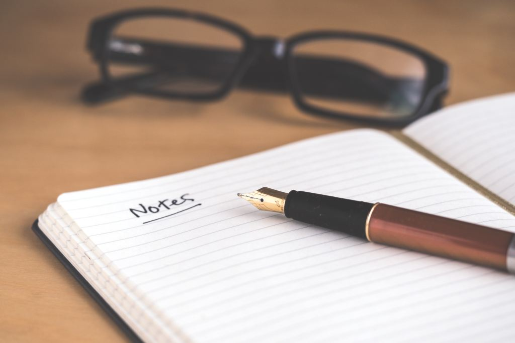 An open notebook, fountain pen and framed glasses sitting on a table