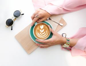 Pexels Photo-Woman Holding a Green Cup of Decorated Coffee