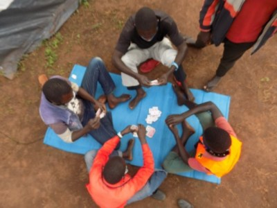 Children playing cards (left) and football (right), play therapy is one of MHPSS approach that was used by CAFOMI at Zeu IQC. Photo credit N.S. Mugarura (left) & Nyokabi Kahura