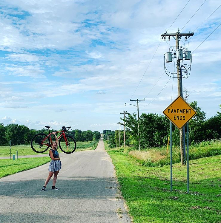 "Alyssa holds her bike with one arm, overhead, standing on a gravel road next to a yellow, diamond road sign that says, ""Pavement Ends""."
