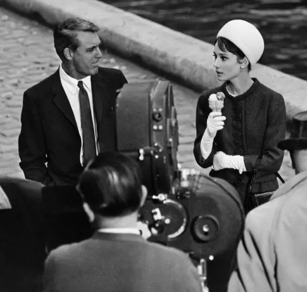 1963: Audrey Hepburn (1929 - 1993) eats an icecream while chatting to Cary Grant (1904 - 1986). They are in Paris for the filming of a scene for 'Charade', directed by Stanley Donen. (Photo by Alan Band/Keystone/Getty Images)