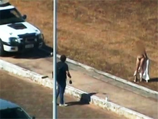 Em viatura, policiais observam ensaio sensual de modelo próximo ao Teatro Nacional, em Brasília (Foto: Reprodução)