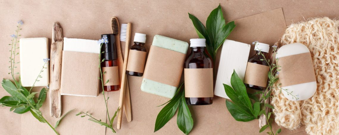 Bath natural accessories and skin care cosmetics - solid soap and shampoo, bamboo toothbrushes, essential oils, zero waste theme on beige background with floral elements. Mock up, copy space