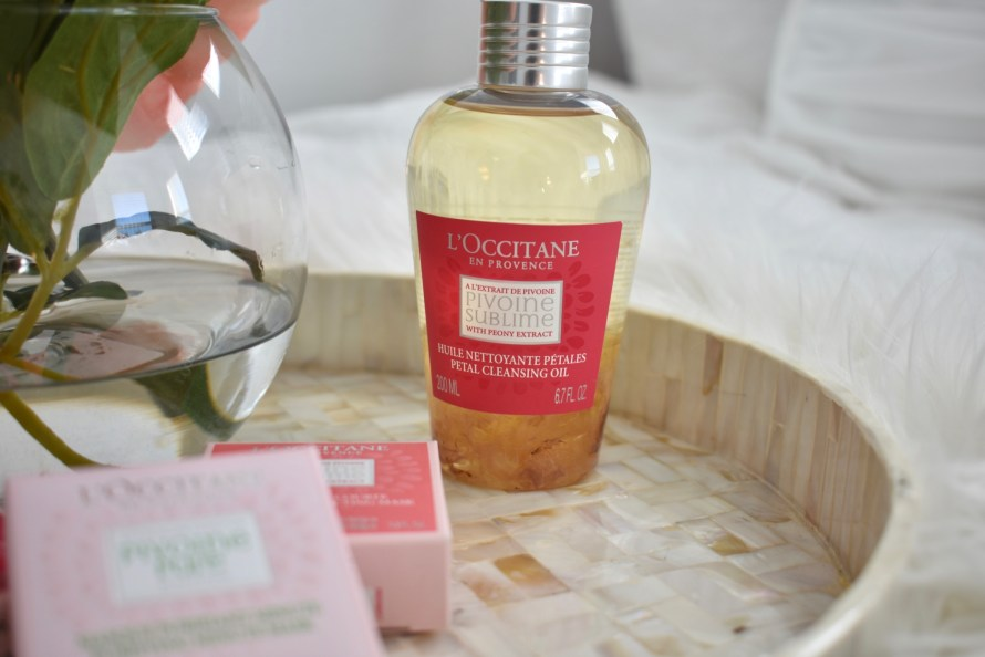 L'Occitane Peony face masks and oil cleanser on mother of pearl tray and faux sheep skin rug