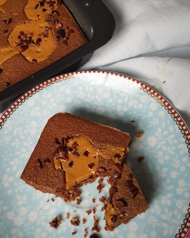 Angeschnittener Peanutbutter Brownie auf hellblauem Kuchenteller. Im linken oberen Eck ist die Browniebackform zu sehen.