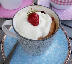Veganer Erdbeer-Tassenkuchen in auf einem hellblauen Unterteller mit Sahnehaube und einer Erdbeere dekoriert.