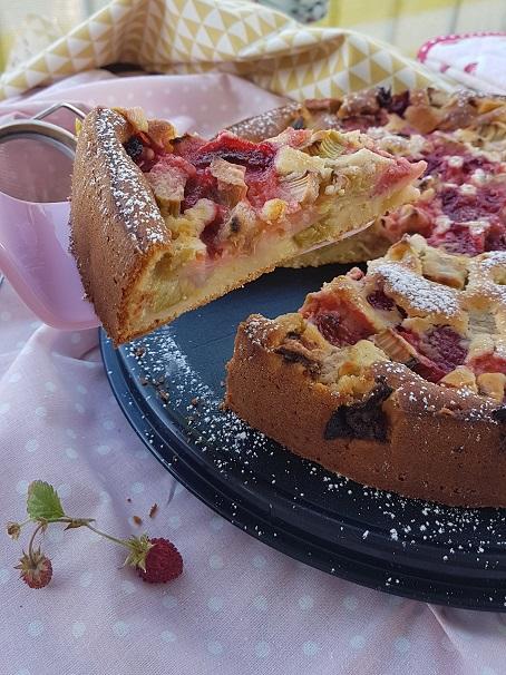 Ein Stück Erdbeer Rhabarberkuchen von Cake Confession auf einem rose Kuchenheber wird gerade vom gesamten Kuchen abgehoben