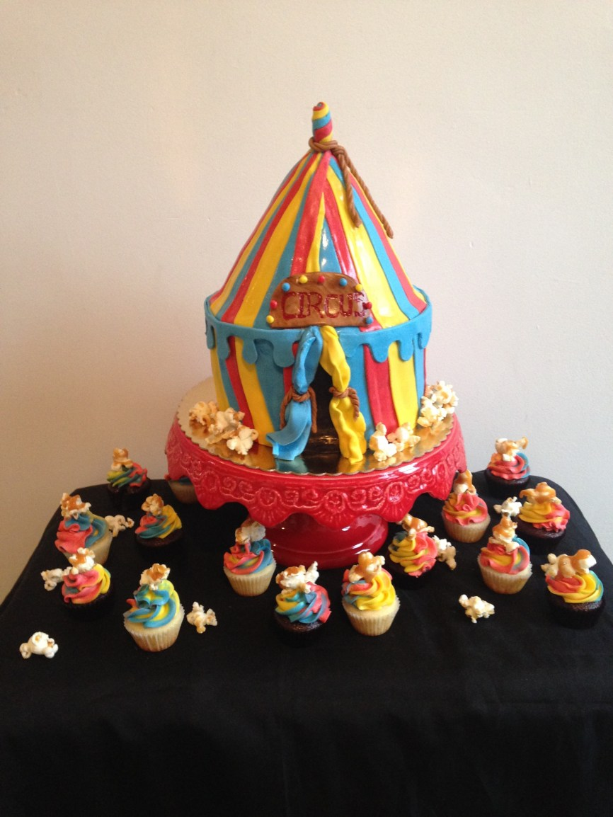 chocolate and vanilla circus tent cake with chocolate and vanilla cupcakes with salted caramel popcorn on top.