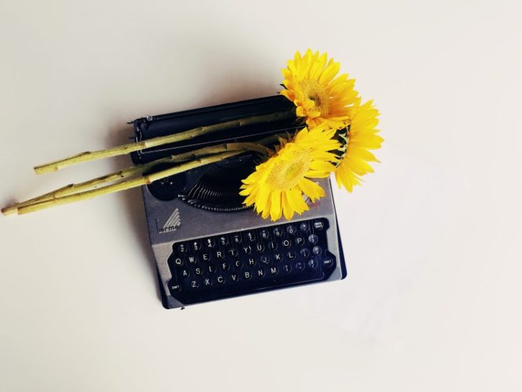 Yellow sunflowers strewn over a vintage hermés typewriter.