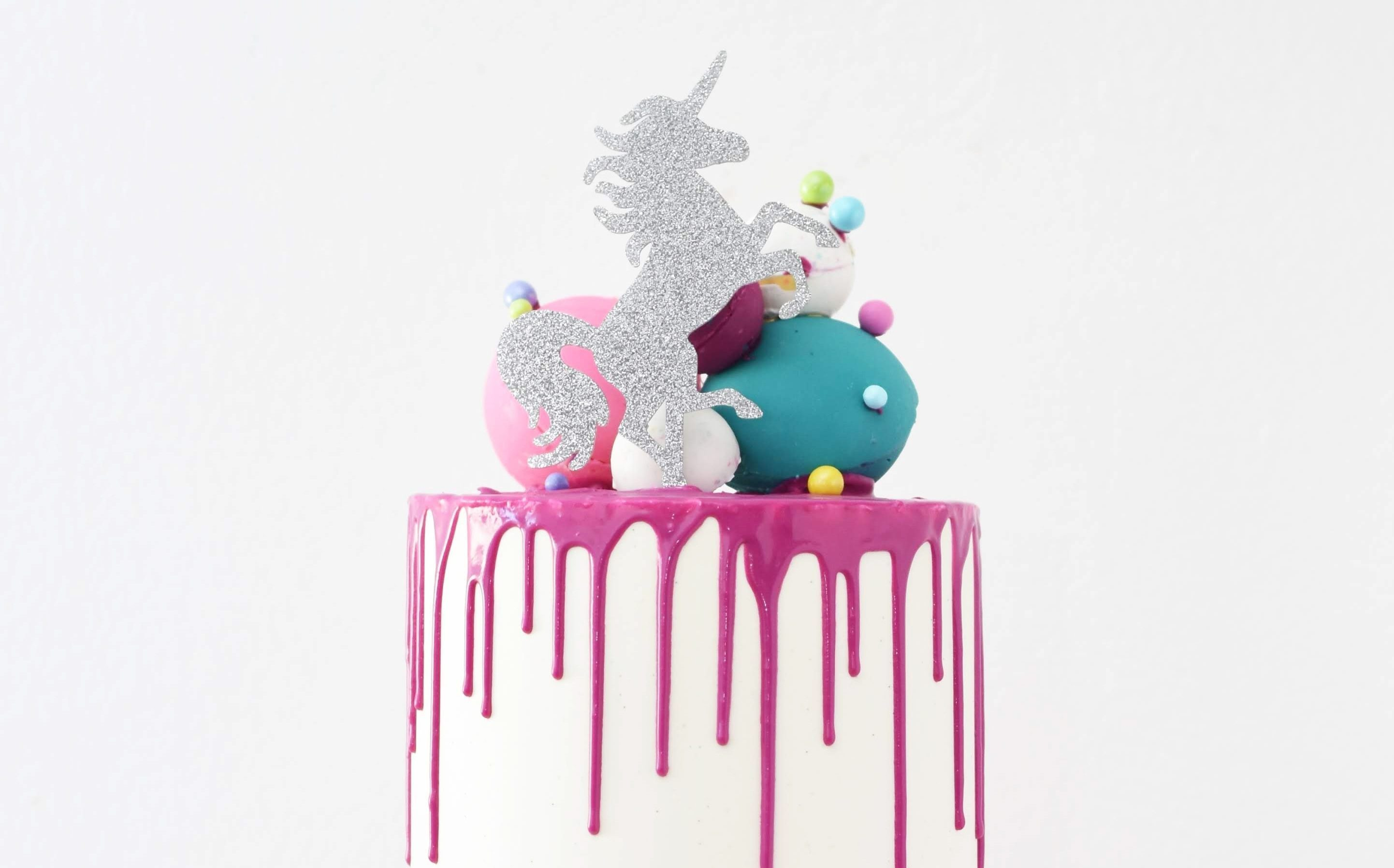 Grand cake with unicorn figure on top. Pink icing drizzle.