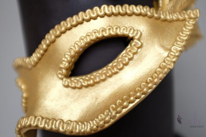 gold and black tiered masquerade cake mask closeup
