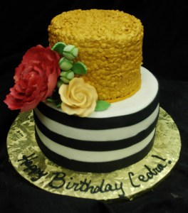 Two-tiered round cake in gold, black, white