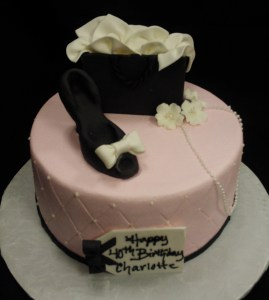 Sculpted pink cake with black shoe and purse
