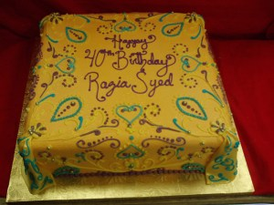 Square gold cake with blue and maroon swirls