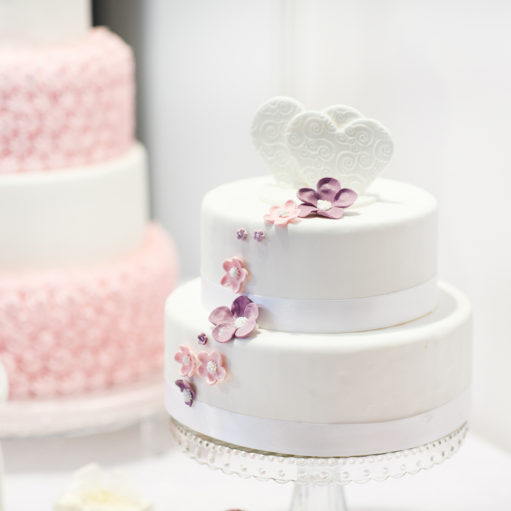 White two tiered wedding cake with pink flowers