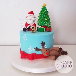 Bolo decorado de Natal: Papai Noel entalado na chaminé, árvore de Natal, rena, presentes e neve. Feito por Cake Studio ( contato@cakestudio.com.br )