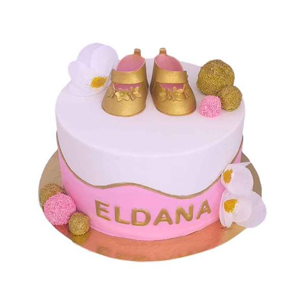 A pink and white Cake topped with Golden Shoes and Golden Cakepops