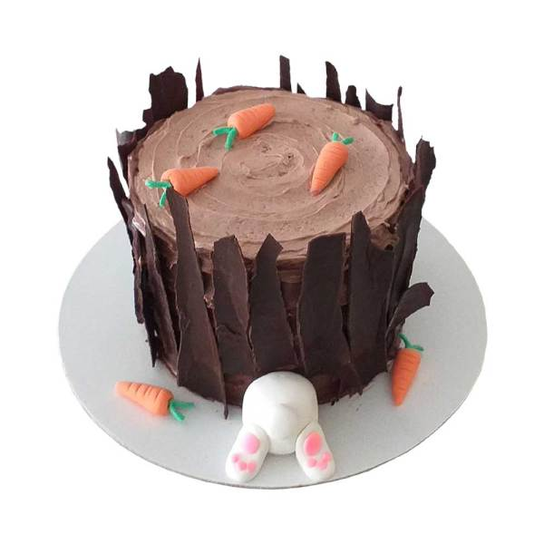 A cake with a bunny stuck inside a log. Log has carrots on top of it.