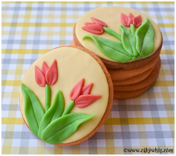 Easy Decorated Tulip Cookies on a Checkered Yellow and Gray Background