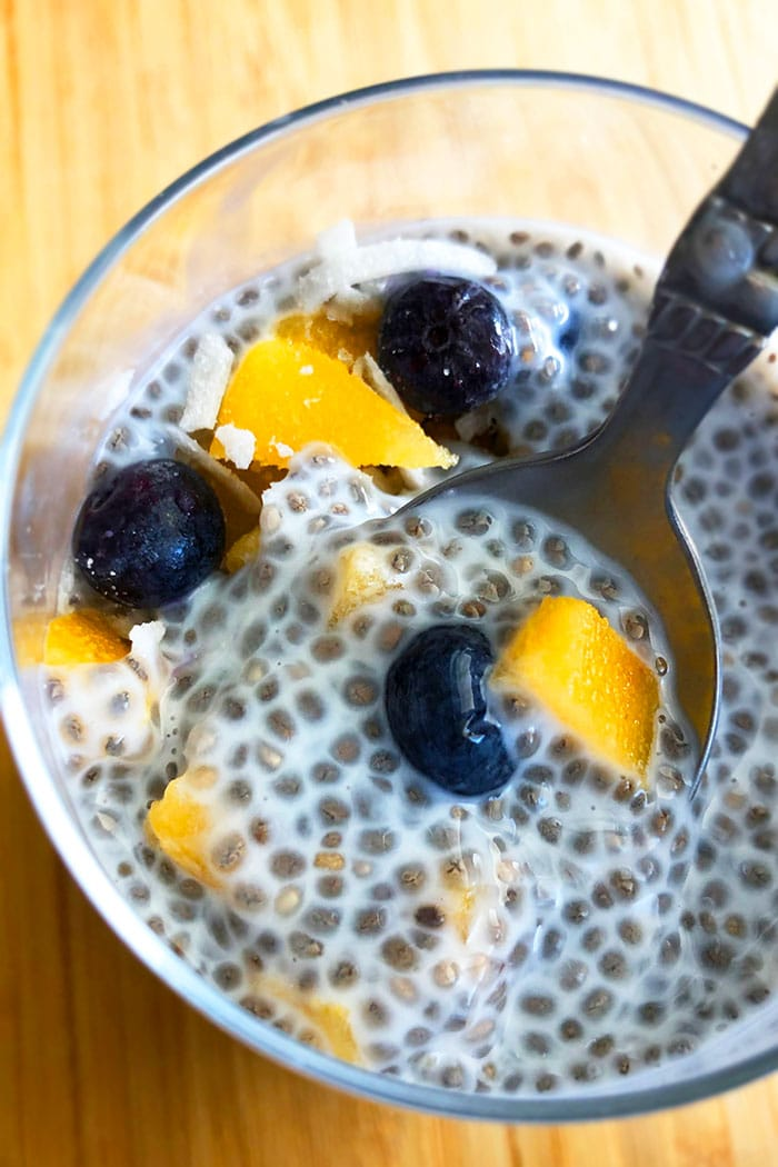 Spoonful of Easy Vanilla Chia Seed Pudding With Fresh Fruits in a Clear Cup