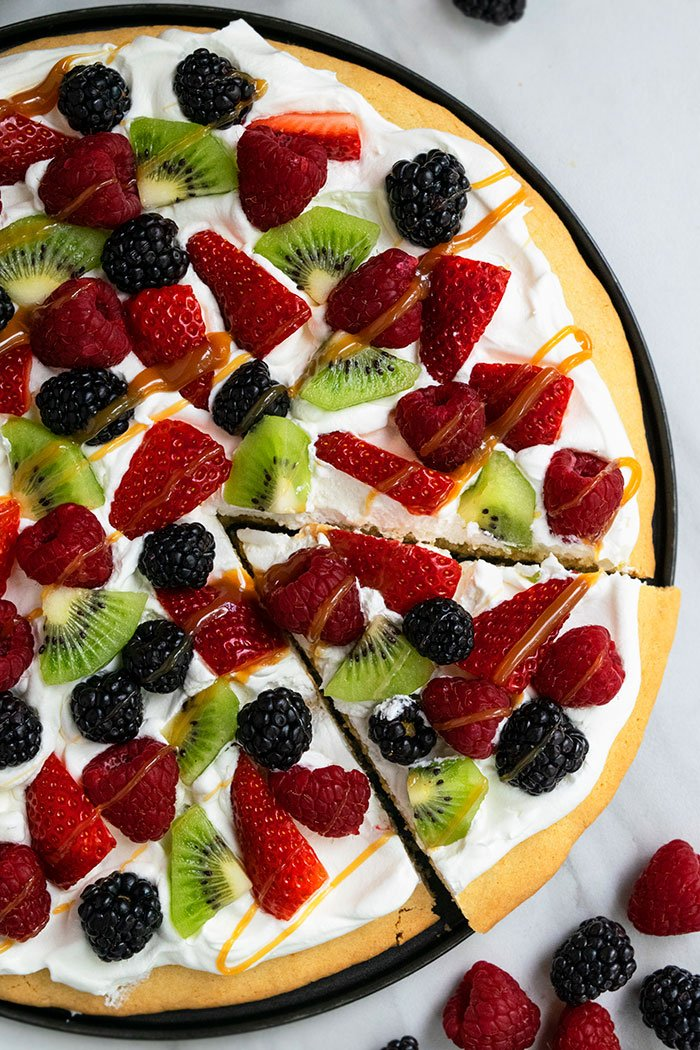 Easy Sugar Cookie Fruit Pizza on Black Plate With A Slice Cut Out