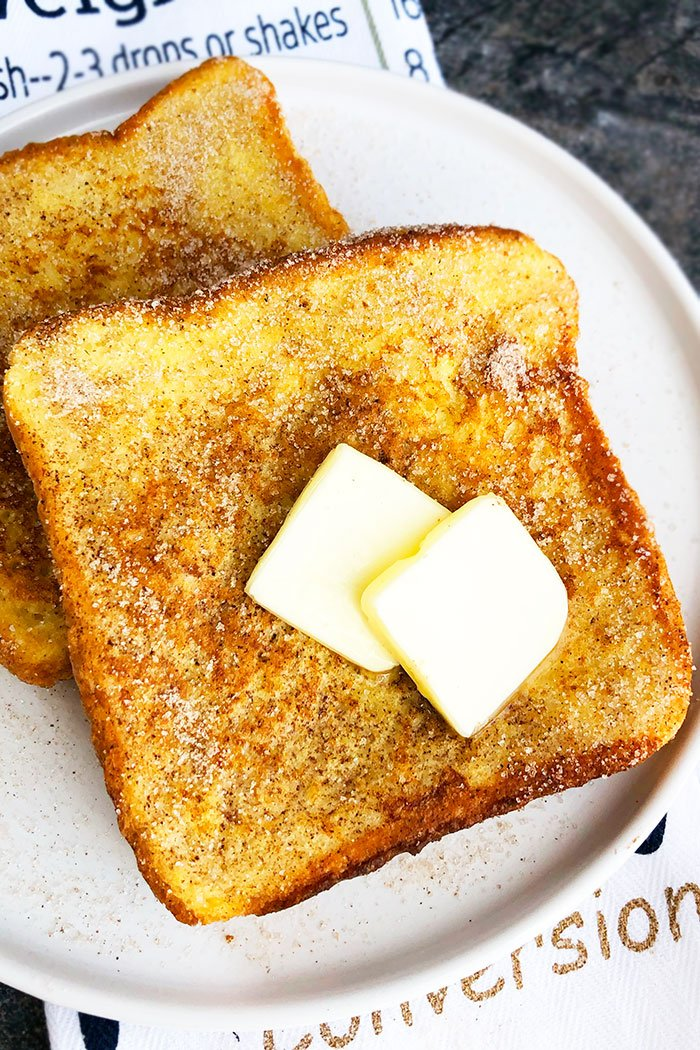 Easy Cinnamon French Toast on White Plate Topped with Sliced Butter