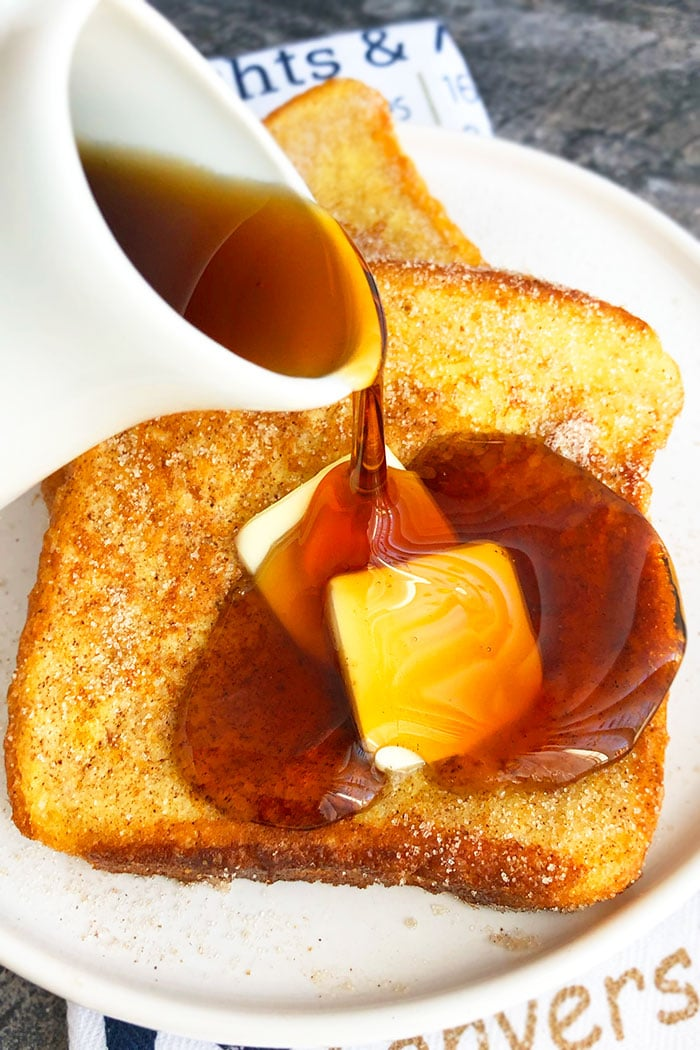 Syrup Being Poured on Fluffy French Toast on White Plate