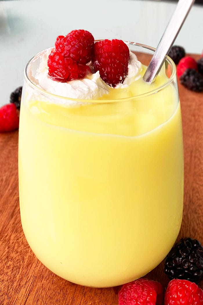 Easy Vanilla Pudding in Clear Glass Cup Topped With Whipped Cream and Raspberries