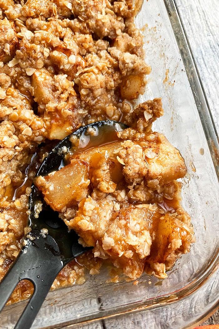 Closeup Shot of Spoonful of Best Caramel Apple Crisp in Glass Dish
