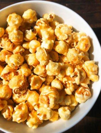 Easy Homemade Caramel Corn in White Bowl on Dark Wood Background