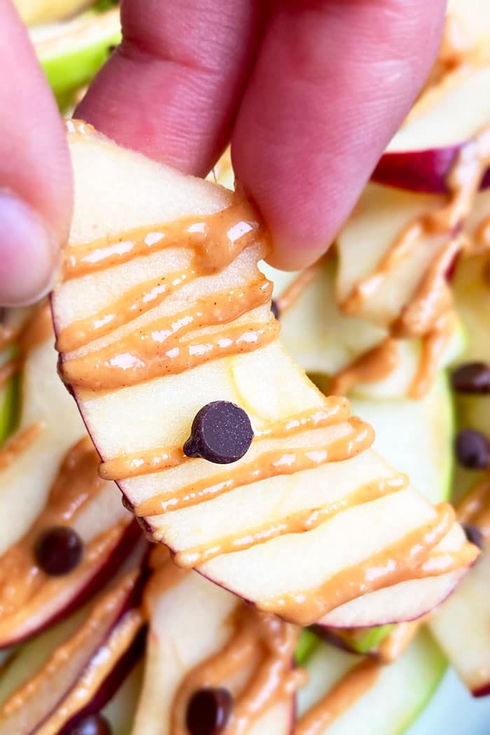Closeup Shot of Holding an Apple Slice with Peanut Butter and Chocolate Chips