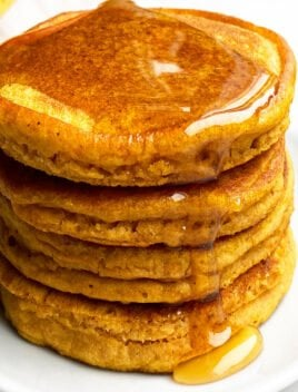 Stack of Pumpkin Pancakes with Maple Syrup Topping on White Plate