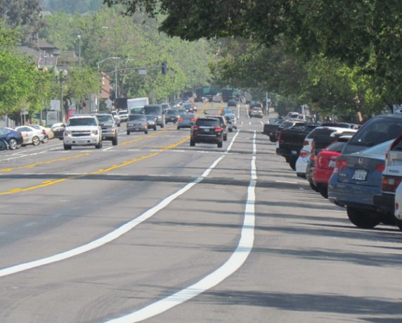 There is plenty of room fr bike lanes on Grand Avenue now that the road has been slimmed from two lanes in each direction to one each, plus a median. This new configuration makes better use of the roadway than giving cars ways to speed around eachother or double park. Photo: Melanie Curry/Streetsblog