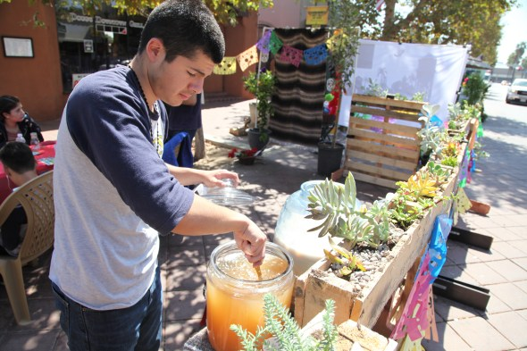 Student from Anaheim High School serving up aguas frescas to passersby. Students from Anaheim high school wanted to celebrate the city's Mexican culture and themed its booth around Dia de Los Muertos-Day of the Dead. Photo by Kristopher Fortin