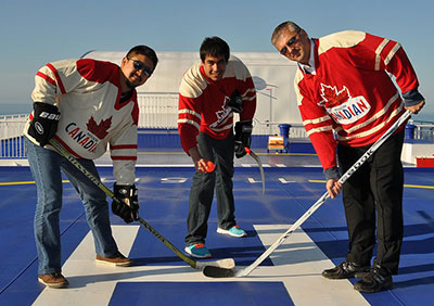 Left to right: Vic Lo, Richard Loat (founder) and Captain Scott Chant faceoff in Five Hole for Food's first ever hockey game on a boat while traveling from Newfoundland to Nova Scotia during the 2011 tour.