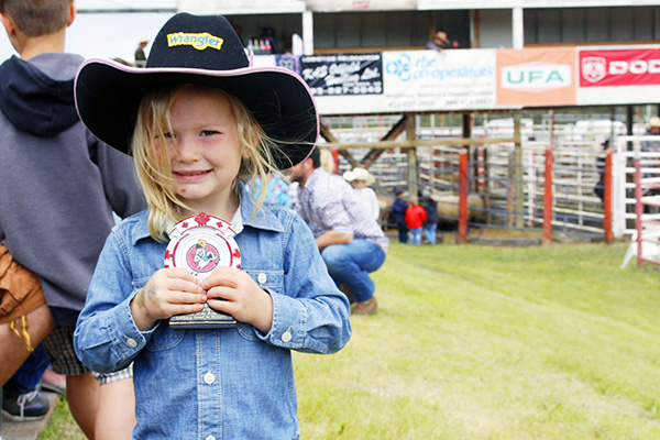 Darren Nelson proudly holds her sheep riding trophy on Saturday, June 16 at her first competition. Photo by Casey Richardson.