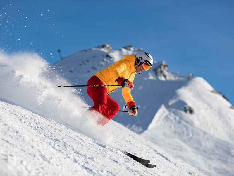 person in yellow jacket and red pants skiing