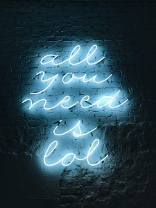 """Neon sign on wall """"all you need is lol"""""""