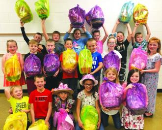 AES students shown with some of the 200 Easter baskets given in memory of Ollidene Hall are, left to right, first row, Kaleb Fletcher, Joel Beall, Lilly Falls, Zemirah Hardman, Paisley Cummings, Isabella Metz; second row, Chelsea Bailey, Trevir Mayle, Kruz Brenneman, Sam Bailey, Alex Starcher, Kynlee Brenneman, Paisley Perkins; third row, Charter Cottrell, Brennen Carpenter, Izabella Zwoll, Brylee Brenneman, Travis Thomas and Christian Rogers.