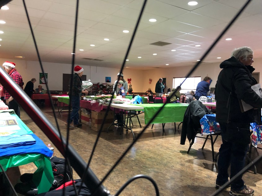 Looking through a bike wheel across a room of crafters.