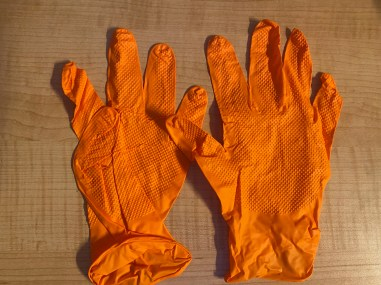 Two orange rubber surgical gloves side by side.