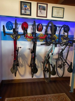 Bikes hanging in the bike closet with red lighting from the ceiling and pictures on the wall.