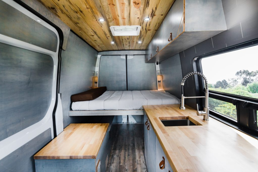 Camper conversion interior with tongue in groove ceilings, kitchen, bed and fridge box.