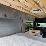 camper van bed and kitchen area with overhead cabinets.