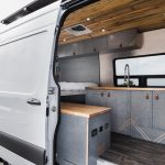 Mercedes Sprinter van conversion with tongue in groove ceilings, custom cabinetry, shower, refrigerator and kitchen,