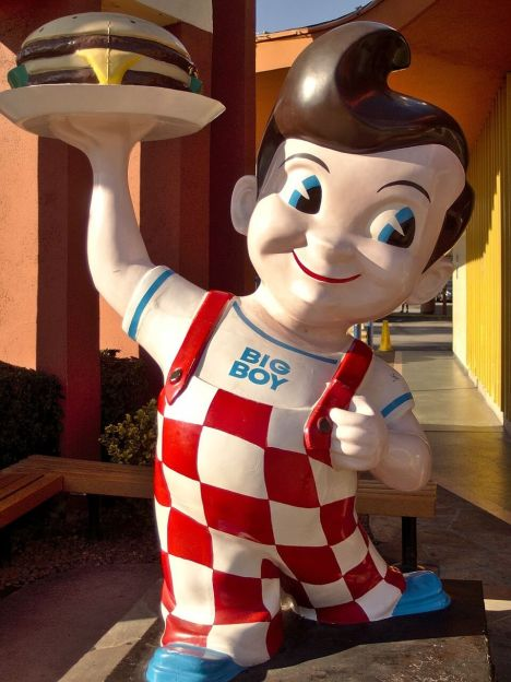 Statue of a small boy holding a burger on a tray outside a Bob's Big Boy restaurant