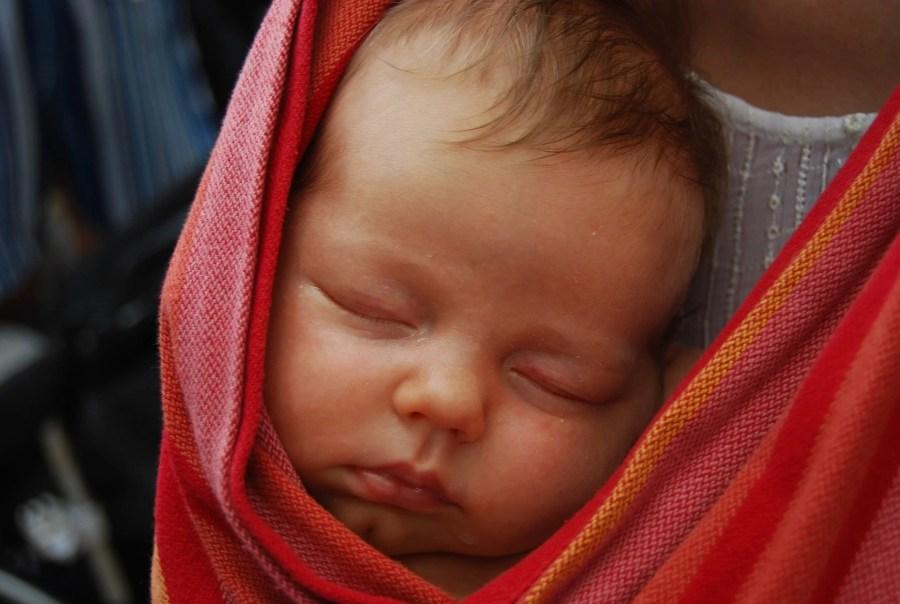 Bébé endormi contre son père dans une écharpe de portage