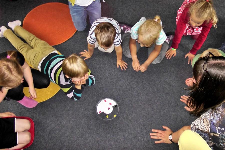 Groupe d'enfants installé en cercle autour d'un jouet à la crèche