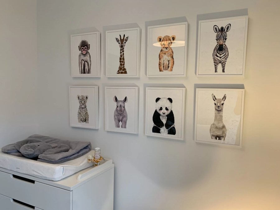 Chambre de bébé ayant pour décoration murale des cadres représentant des animaux