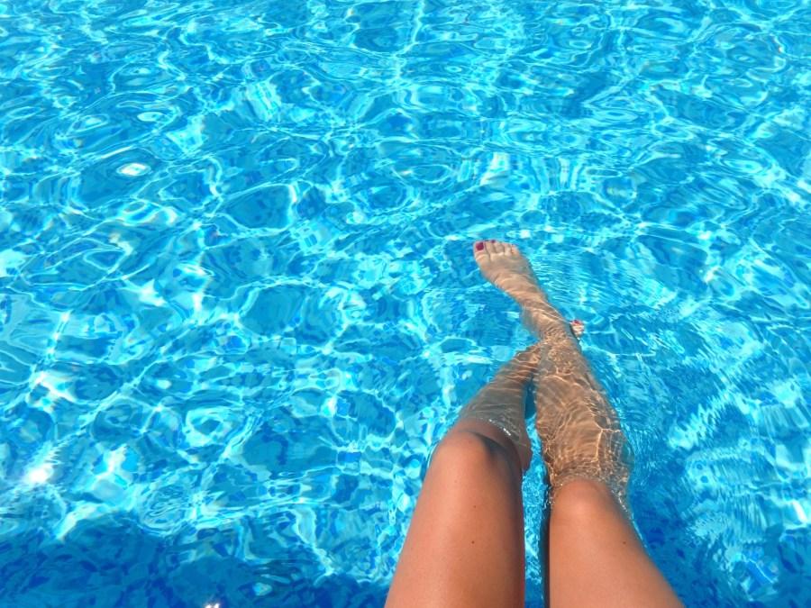 Femme plongeant ses pieds dans une piscine d'eau claire